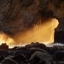 Sunlight shines through the arch at Pfieffer Beach in Big Sur, California
